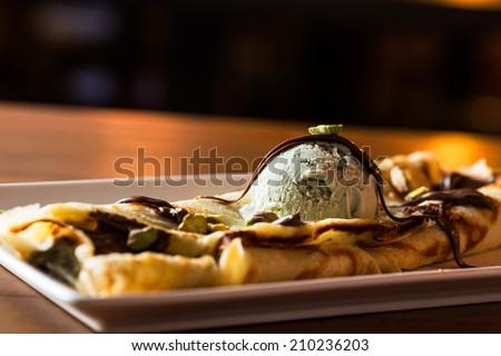 Delicious pistachio ice cream with chocolat crepe. - stock photo