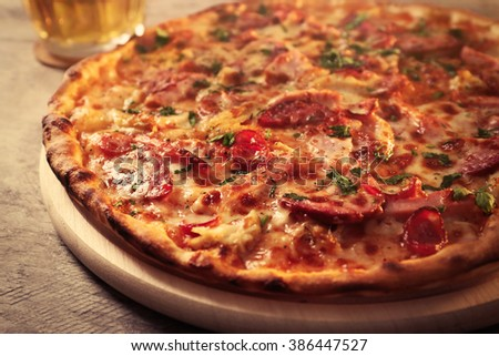 Delicious pizza  and glass of beer are on wooden table, close up - stock photo