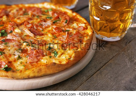 Delicious pizza  and glasses of beer are on wooden table, close up - stock photo
