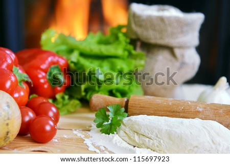 delicious pizza dough, spices and vegetables on wooden table - stock photo