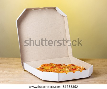 delicious pizza in package on yellow background - stock photo