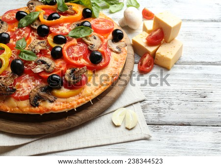 Delicious pizza served on wooden table - stock photo