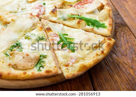 Delicious pizza with chicken, parmesan, tomatoes, white sause and fresh arugula - thin pastry crust at wooden background - stock photo