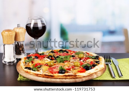 Delicious pizza with glass of red wine and spices on wooden table on room background - stock photo