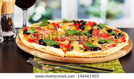 Delicious pizza with glass of red wine and spices on wooden table on window background - stock photo