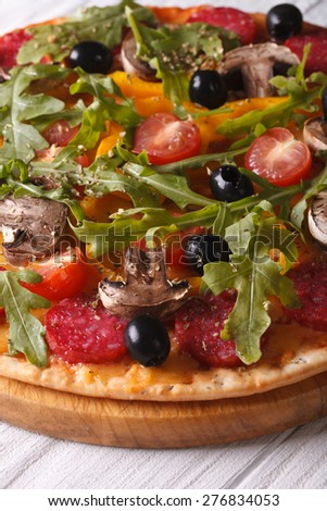 Delicious pizza with herbs, vegetables and salami close up on the table. vertical  - stock photo
