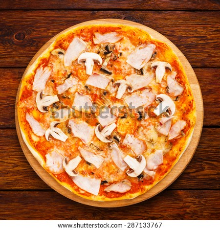 Delicious pizza with mushrooms and smoked chicken meat - thin pastry crust isolated at wooden background, above view - stock photo
