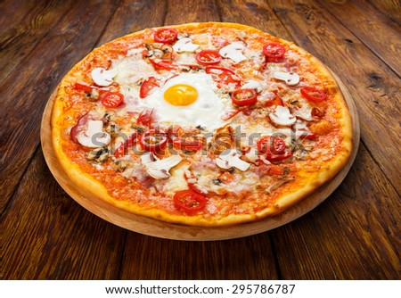 Delicious pizza with mushrooms, bacon, cherry tomatoes and egg - thin pastry crust at wooden background on wooden desk - stock photo