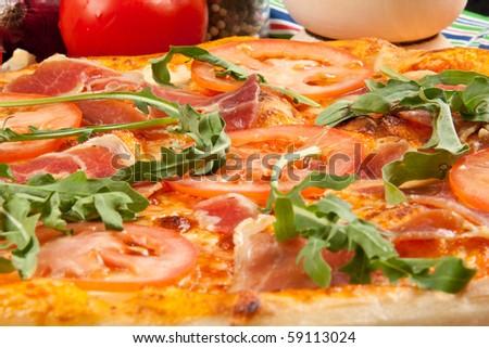 Delicious pizza with peosciutto crudo and rucola - stock photo