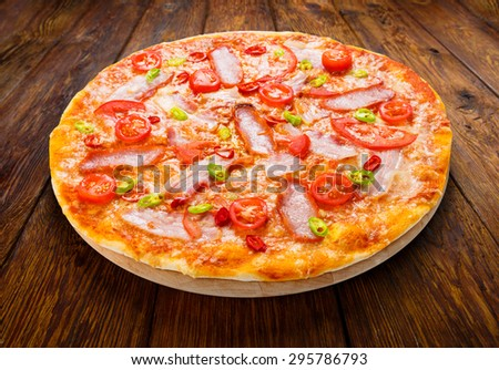 Delicious pizza with red and green hot chili peppers, bacon and cherry tomatoes - thin pastry crust at wooden background on wooden desk - stock photo