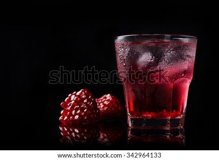 Delicious pomegranate cocktail on the black background - stock photo
