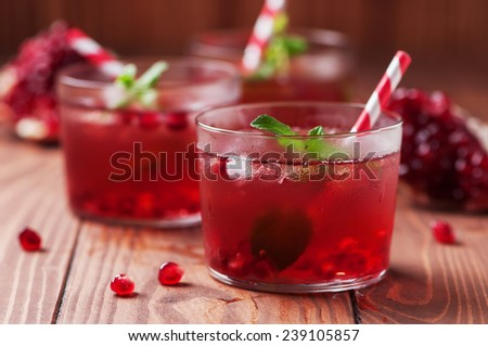 delicious pomegranate cocktail with mint and ice on the wooden table - stock photo