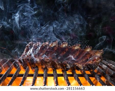 Delicious pork spareribs on cast-iron grill grate, garden barbecue. - stock photo