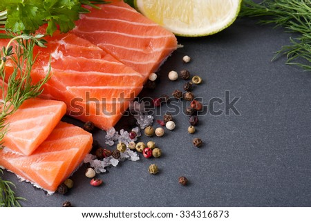 Delicious portion of fresh salmon fillet with aromatic herbs, spices and vegetables - healthy food, diet or cooking concept - stock photo