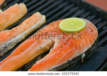 Delicious  portion of fresh salmon fillet with lime on a grill or BBQ - stock photo