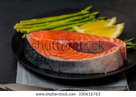 Delicious portion of fresh salmon steak with aromatic herbs, spices and vegetables on black background - healthy food, diet or cooking concept - stock photo