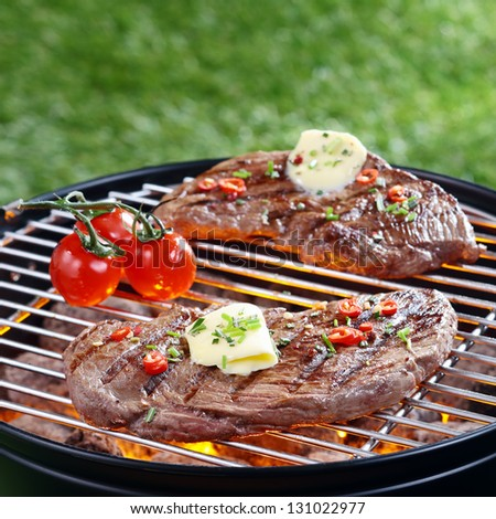 Delicious portion of lean steak topped with butter and herbs grilling on a barbecue over red hot coals outdoors on the lawn - stock photo