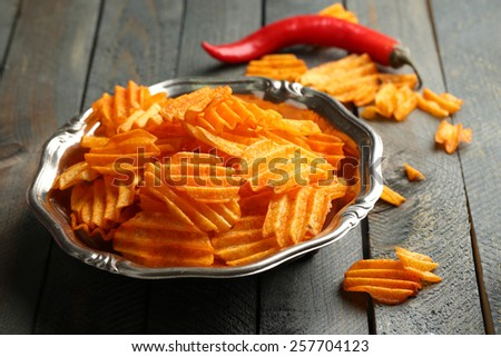 Delicious potato chips on plate on wooden table close-up - stock photo