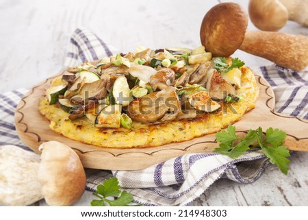 Delicious potato pancake with mushroom sauce and fresh porcini mushrooms on white wooden textured background. Traditional europen culinary eating, rustic styles.  - stock photo