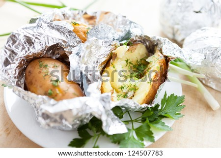 delicious potatoes cooked in foil with herbs, close up - stock photo