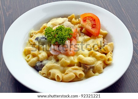 Delicious prawn macaroni pasta with cheese and mushrooms on a white plate. - stock photo