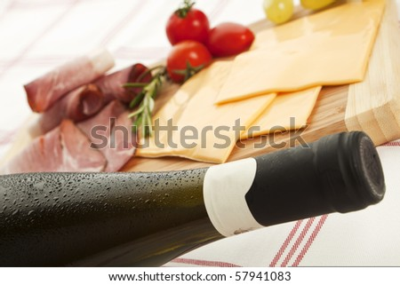 Delicious prosciutto and ham plate with rosemary, grapes and a white wine bottle with waterdrops. - stock photo