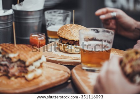 Delicious Pub Food. Burgers And Glasses Of Beer On Wooden Plates - stock photo