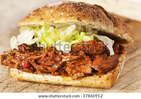 Delicious pulled pork sandwich on wood board - stock photo
