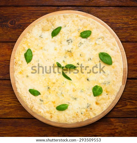 "Delicious ""Quaddro formaggi""  four cheese pizza with parmesan, cheddar, mozzarella and  blue cheese decorated with basil leaves - thin pastry crust at wooden background on wooden desk above view - stock photo"