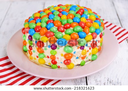 Delicious rainbow cake on plate on table close-up - stock photo