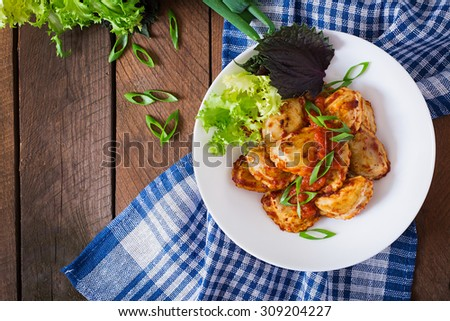 Delicious ravioli with tomato sauce and green onions. Top view - stock photo