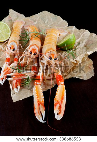 Delicious Raw Langoustines with Lime and Rosemary on Parchment Paper closeup on Dark Wooden background - stock photo