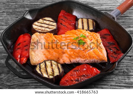 Delicious red fish salmon steak fillet on a iron grill pan with grilled bell pepper and slices of aubergine, close-up, view from above - stock photo