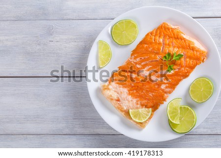delicious red fish salmon steak fillet on a white dish with sliced lime and parsley, on a wooden table, blank space left, view from above  - stock photo