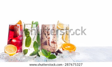 delicious refreshing summer drinks . Sangria , lemonade, iced chocolate drink , a mojito on a white background . Ice cubes around glasses with drinks . Natural collage of beverages. copy space - stock photo