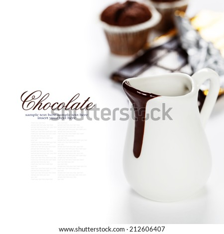 Delicious rich and thick chocolate sauce in a jug and assorted chocolates - food and drink - stock photo