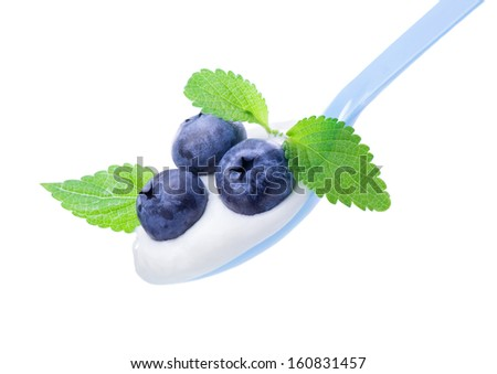 Delicious ripe blueberry on white yogurt and  leaves of mint, in  blue spoon - stock photo