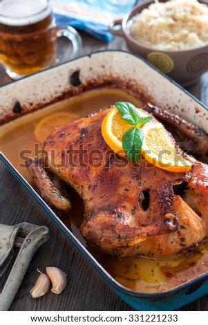 Delicious roasted duck with oranges and beer in a pan, rustic style - stock photo