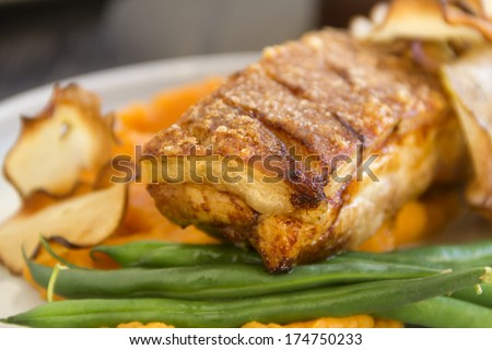 Delicious roasted pork belly with crackling, sweet potato mash and steamed green beans. - stock photo