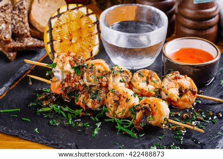 Delicious roasted shrimps on skewers with sauce and lemon - stock photo