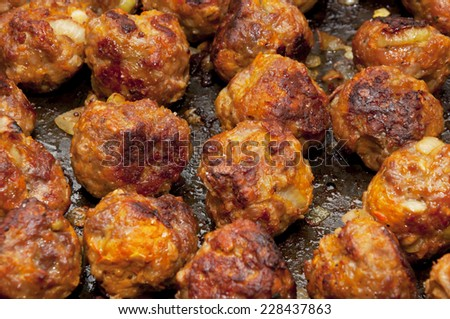 Delicious rustic famous roasted meat balls with carrot and onion on the tray just from oven - stock photo