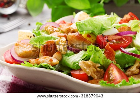 Delicious salad with chicken, nuts, egg and vegetables. - stock photo