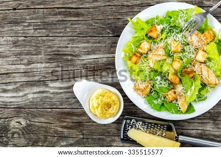 Delicious salad with croutons, grilled chicken breast, grated parmesan cheese and cos lettuce,  with sauce in the gravy boat, simply and healthy recipe, horizontal top view - stock photo