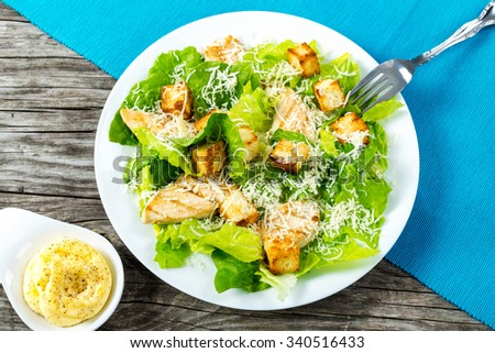 Delicious salad with croutons, grilled chicken breast, grated parmesan cheese and cos lettuce, with sauce in the gravy boat, classic recipe, close-up, horizontal top view - stock photo