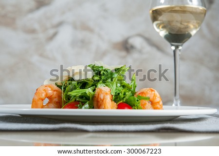 Delicious salad with shrimps, arugula, cherry tomatoes and Parmesan cheese, seasoned with balsamic sauce on served for dinner restaurant table  - stock photo