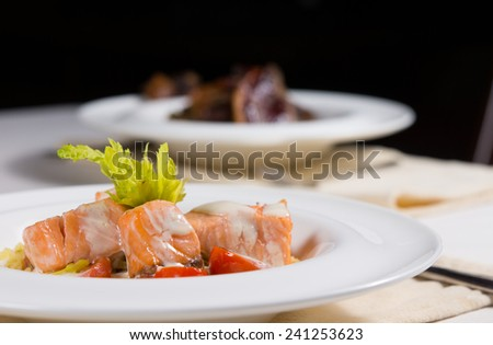 Delicious salmon appetizer with bite-sized portions of grilled salmon drizzled in a creamy sauce and served with fresh lettuce, low angle view at a restaurant table - stock photo
