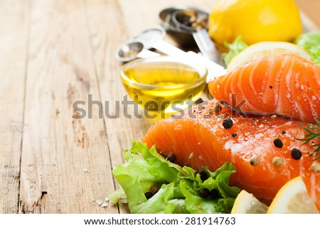 Delicious salmon fillet, rich in omega 3 oil, aromatic spices and lemon on fresh lettuce leaves on rustic wooden background. Healthy food concept. With copy space. Selective focus. - stock photo