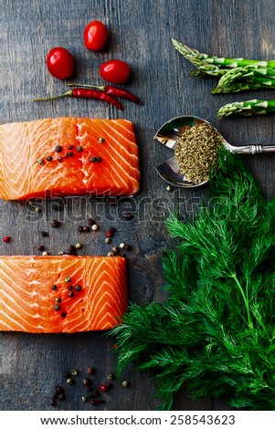 Delicious salmon fillet with asparagus and aromatic herbs, spices and vegetables over wood background- healthy food, diet or cooking concept. Top view. - stock photo