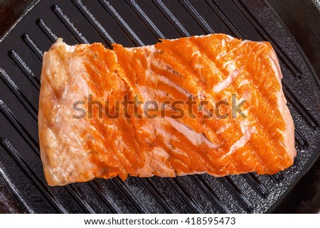 Delicious salmon steak on a iron grill pan, close-up, view from above - stock photo