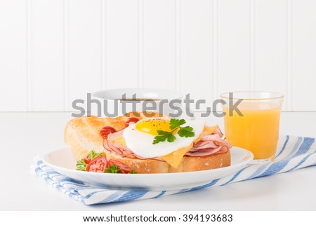 Delicious sandwich of fried egg, ham and cheese served with coffee and juice. - stock photo